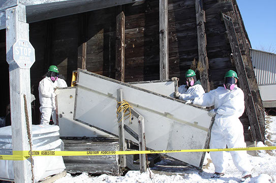 Workers moving hazardous materials out of a building